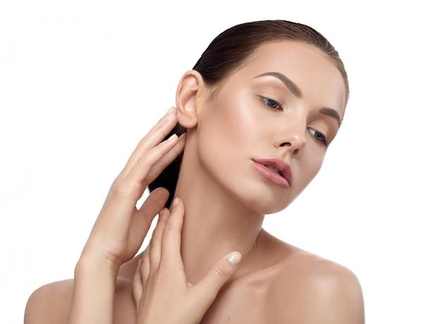 Bonita modelo con rasgos faciales maravillosos posando tocando su cuello con ternura.