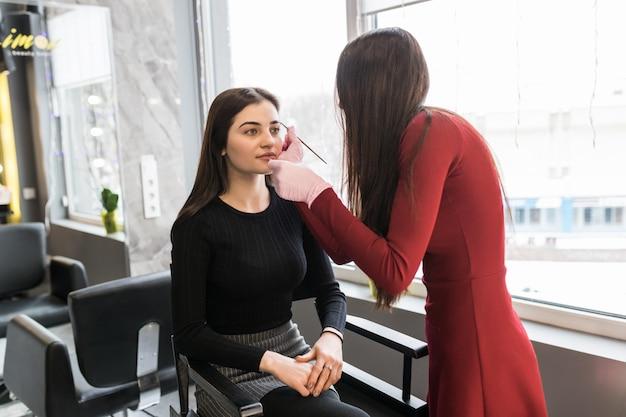 Bonita modelo en ropa negra haciendo procedimiento de maquillaje en salón especial