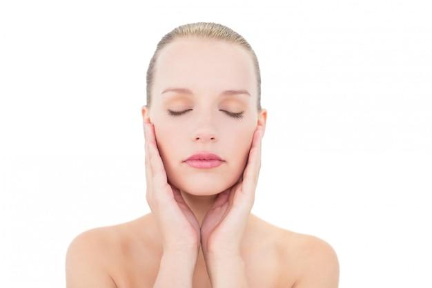 Bonita modelo rubia sosteniendo sus mejillas con los ojos cerrados.