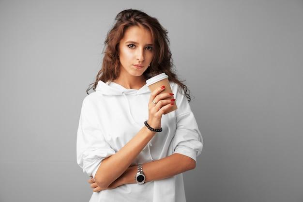 Bonita morena joven sosteniendo una taza de café sobre un fondo gris