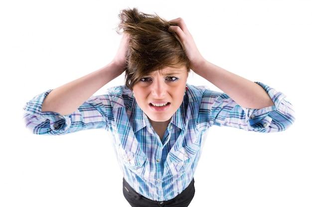 Bonita morena recibiendo un dolor de cabeza con las manos en la cabeza