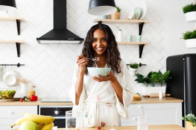 Bonita mujer africana está comiendo avena en la mañana