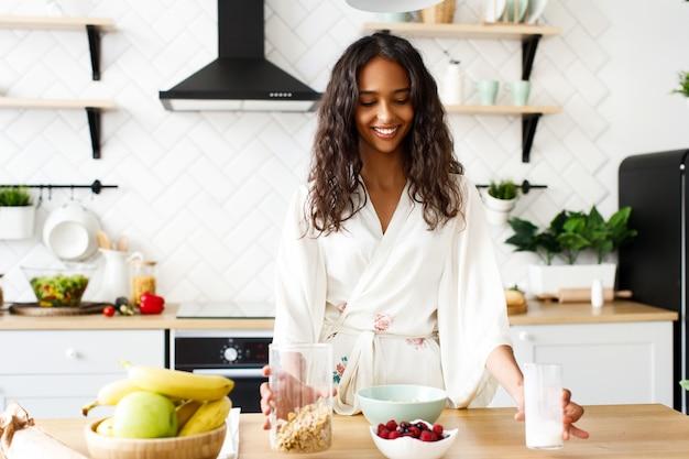 Bonita mujer africana está haciendo un desayuno saludable