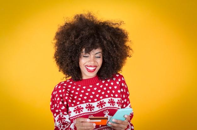 Bonita mujer afroamericana, compras navideñas con teléfono inteligente y tarjeta de crédito, fondo amarillo,