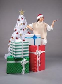 Bonita mujer alrededor de regalos de navidad en gris
