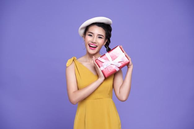 Bonita mujer asiática sosteniendo rojo se presenta con alegría
