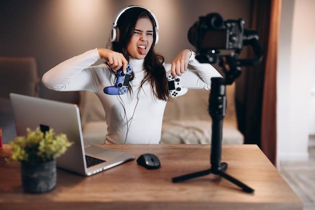 Bonita mujer blogger en auriculares está transmitiendo en vivo hablando de videojuegos. influencer mujer joven transmisión en vivo. no me gustó y totalmente decepcionado.