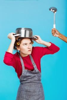 Bonita mujer con una cacerola en la cabeza se esconde del cucharón
