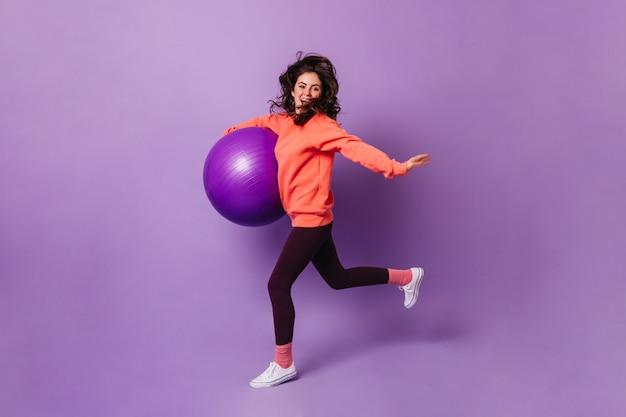 Bonita mujer en calcetines rosas, sudadera naranja y leggings oscuros corre en la pared púrpura con fitball