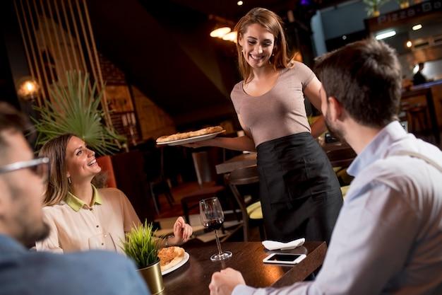 Bonita mujer camarero sirviendo a un grupo de amigos con comida en el restaurante