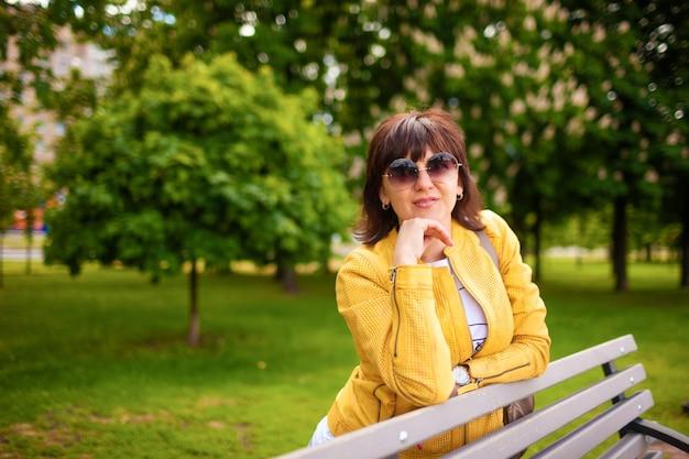 Bonita mujer caucásica atractiva pelirroja en ropa casual y gafas de sol posando en un banco del parque en un día soleado de primavera