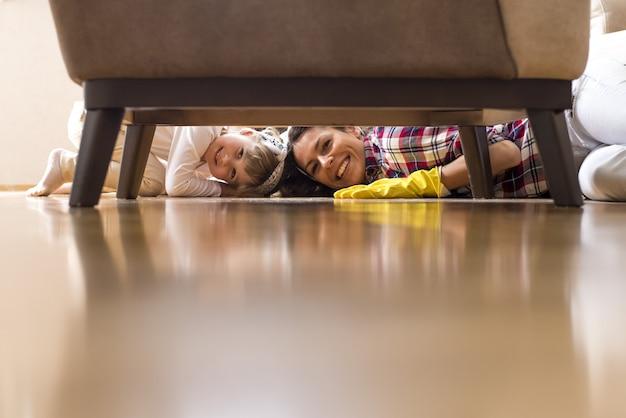 Bonita mujer caucásica y un niño pequeño limpiando la casa juntos y divirtiéndose