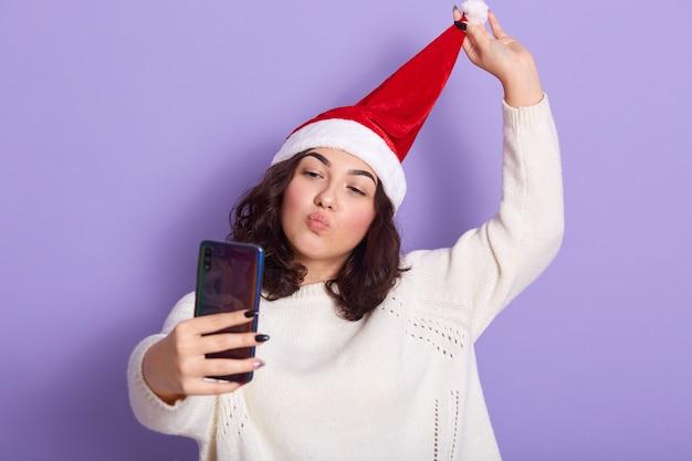 Bonita mujer caucásica vistiendo suéter blanco cálido y sombrero de santa navidad, adorable niña tomando autorretrato