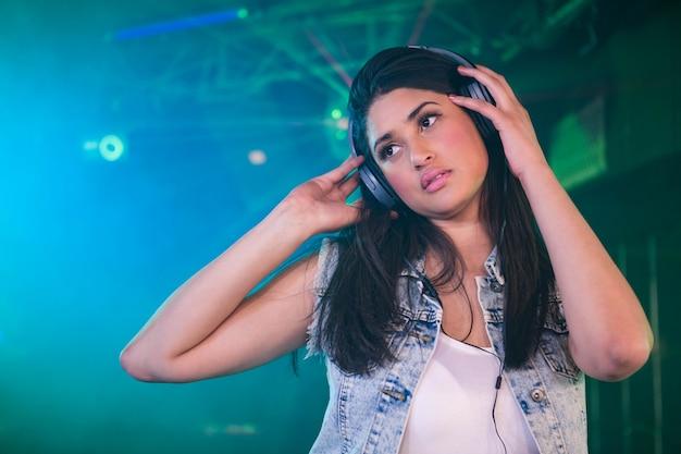 Bonita mujer dj escuchando música en auriculares
