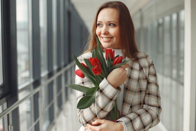 Bonita mujer europea con tulipanes rojos se encuentra en un luminoso salón moderno