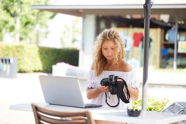 Bonita mujer fotógrafa trabajando con laptop en café