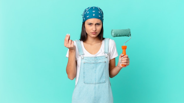 Bonita mujer hispana haciendo capice o gesto de dinero, diciéndole que pague. concepto de casa de pintura