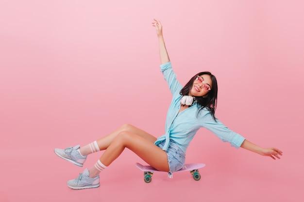 Bonita mujer hispana con piel bronceada agitando las manos mientras está sentado en longboard. chica latina inspirada en gafas de sol posando en patineta