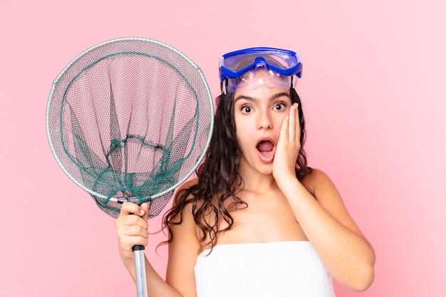 Bonita mujer hispana que se siente conmocionada y asustada con gafas y red de pesca