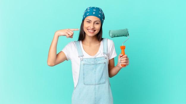 Bonita mujer hispana sonriendo con confianza apuntando a su propia amplia sonrisa. concepto de casa de pintura