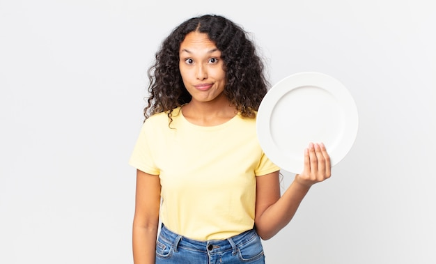 Bonita mujer hispana sosteniendo un plato limpio vacío