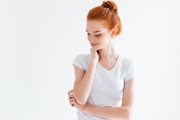 Bonita mujer de jengibre en camiseta mirando hacia abajo