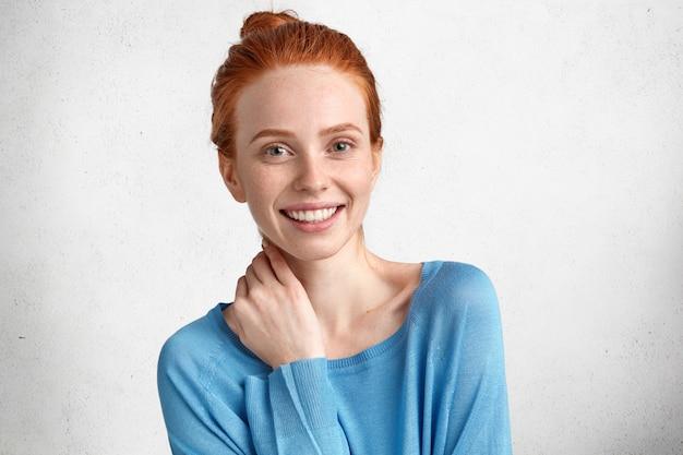 Bonita mujer de jengibre con expresión satisfecha, tiene una amplia sonrisa, se alegra de ser promovida en el trabajo o recibe una bonificación por ser diligente, aislada en blanco