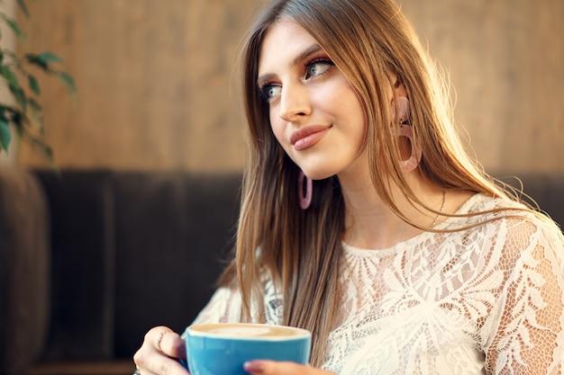 Bonita mujer joven disfrutando de una taza de café en una cafetería.