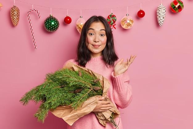 Bonita mujer joven morena tiene un pasatiempo creativo levanta la palma con vacilación, no sabe qué hacer con las ramas de abeto verde se prepara para las vacaciones de invierno posa sobre la decoración navideña en casa