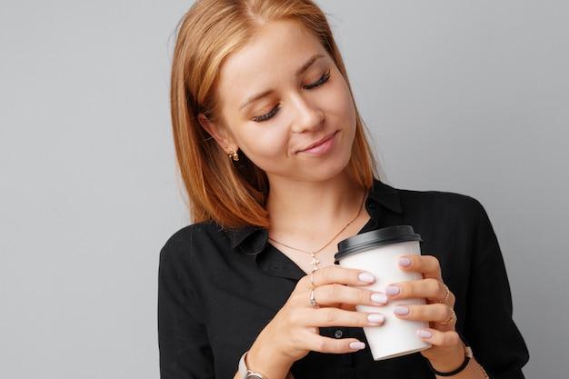 Bonita mujer joven con una taza de café sobre un fondo gris