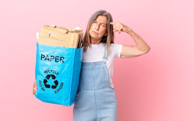 Bonita mujer de mediana edad que se siente confundida y perpleja, mostrando que estás loco reciclando el concepto de cartón