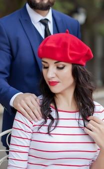 Bonita mujer morena con una gorra roja y una camiseta a rayas sentado en un café al aire libre