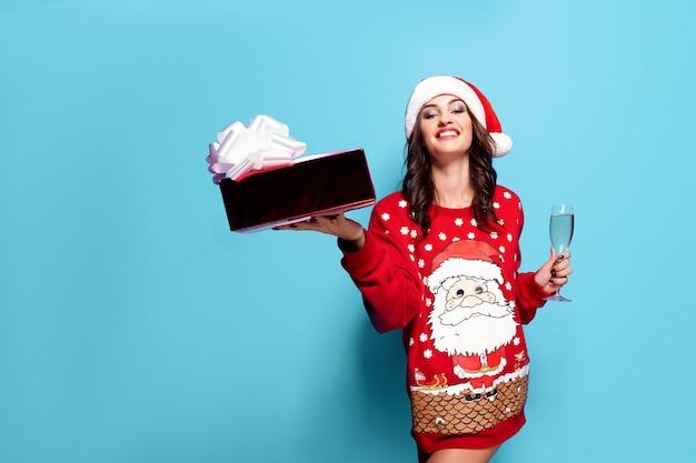 Bonita mujer morena en jersey rojo con santa, copa de champán sobre fondo azul.