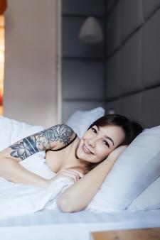 Bonita mujer morena con tatuaje se acuesta en la cama sobre la almohada en la mañana en el apartamento de moda