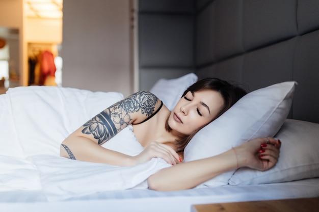 Bonita mujer morena con tatuaje yace en la cama sobre la almohada por la mañana en el moderno apartamento de moda