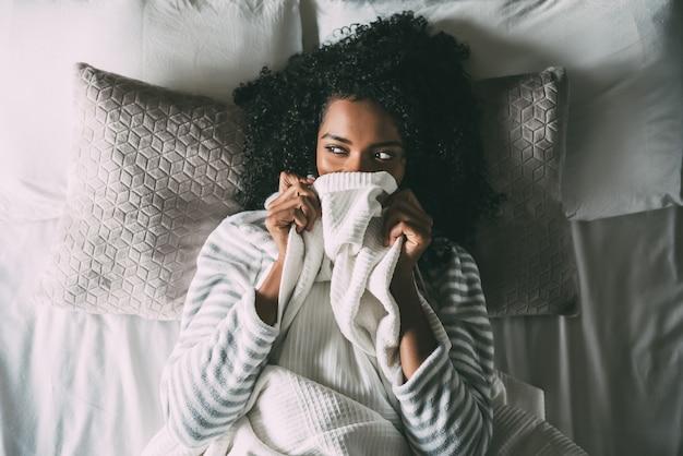 Bonita mujer negra cubriendo su boca con la sábana mirando a otro lado