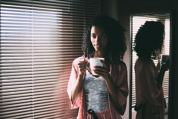 Bonita mujer negra de pie en la ventana con una taza de café