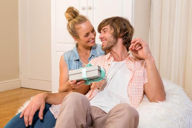 Bonita mujer ofreciendo novio un regalo en la sala de estar