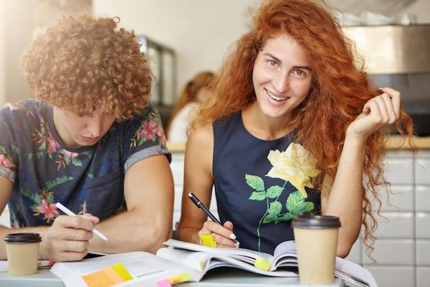 Bonita mujer pecosa sentada en la mesa escribiendo notas ayudando a su compañero de grupo a estudiar