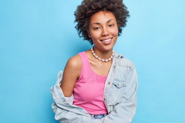 Bonita mujer de pelo rizado viste una camiseta rosa, un collar de chaqueta de mezclilla muestra un hombro desnudo sonríe alegremente aislado en la pared azul