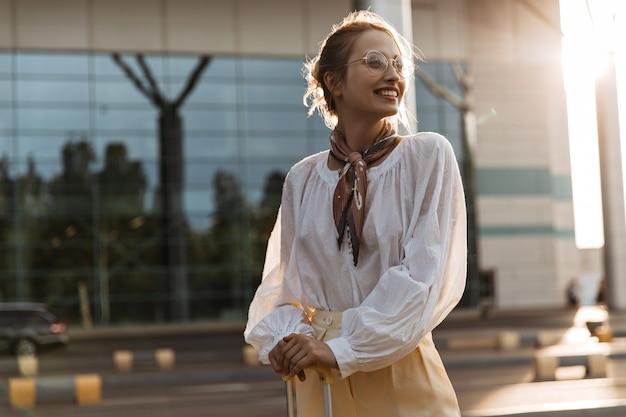 Bonita mujer rubia encantadora en blusa blanca sonríe sinceramente