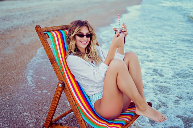 Bonita mujer rubia en forma de corazón gafas de sol, camisa blanca y traje de baño despojado relajante en una tumbona de playa y bebidas cóctel. concepto de vacaciones de verano