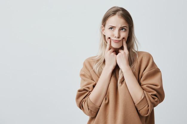 Bonita mujer rubia haciendo una mueca, tocando sus mejillas con los dedos, mirando hacia arriba, con expresión de disgusto. expresión facial y emociones negativas.