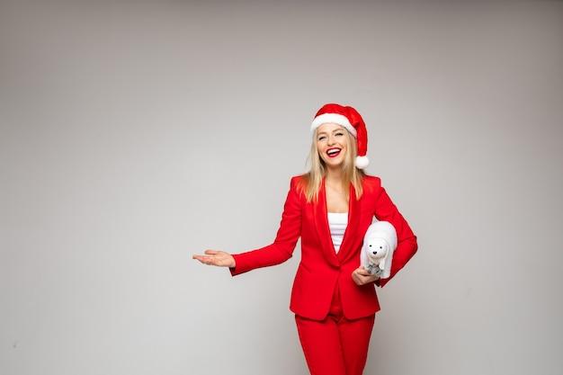 Bonita mujer rubia en traje rojo sostiene un osito blanco y sonríe, imagen aislada sobre fondo blanco