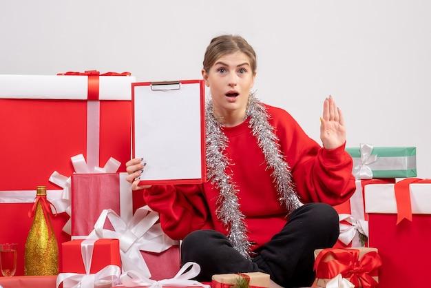 Bonita mujer sentada alrededor de regalos de navidad en blanco