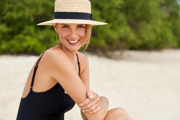 Bonita mujer sonriente con expresión feliz, tiene una piel suave y saludable, se sienta en la playa de arena cerca del océano, se relaja cerca del agua azul turquesa, disfruta de un ambiente tranquilo. la mujer admira la hermosa puesta de sol.