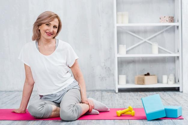 Bonita mujer sonriente sentada cerca de bloques y mancuernas en estera de yoga
