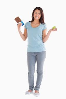 Bonita mujer sosteniendo una barra de chocolate y una manzana