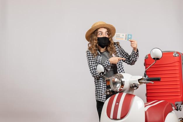 Bonita mujer sosteniendo boleto de pie cerca de ciclomotor gris
