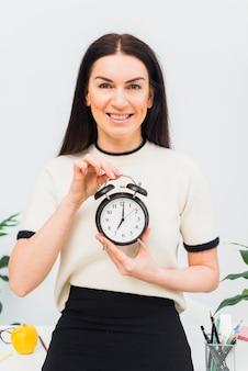 Bonita mujer sosteniendo reloj con 7 am